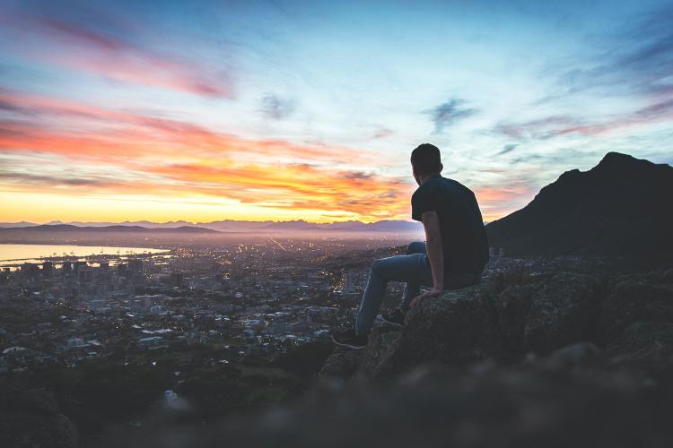 Man sitting on a rock overlooking a colourful sunset