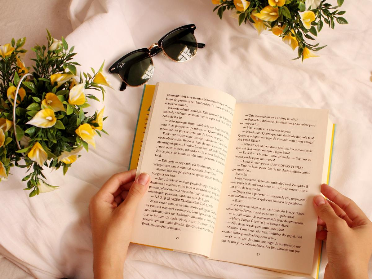 An opened book decorated by surrounding flowers